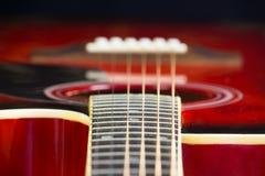 La guitarra roja acústica miente en la tabla, modo de fondo oscuro con una copia de las manos del espacio, jugando en la obra clá Imagen de archivo