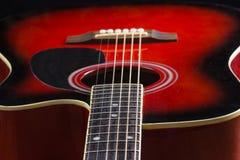 La guitarra roja acústica que miente en la tabla en el fondo con una copia de las manos espacia tocar la guitarra acústica, cierr Imagen de archivo libre de regalías