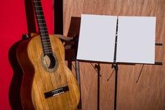 La guitarra, la silla y el atril exhibieron con un fondo de madera y rojo fotos de archivo libres de regalías