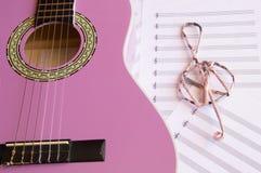 La guitarra violeta para los niños con la clave de sol en las hojas de música apoya Foto de archivo