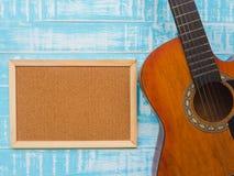La guitarra y el tablero en fondo de madera azul de la textura Música DA fotografía de archivo libre de regalías