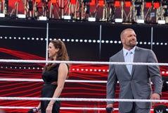 La H tripla e Stephanie McMahon sorridono in mezzo all'anello Immagini Stock Libere da Diritti