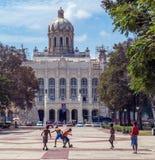 LA HABANA, CUBA - 1 DE ABRIL DE 2012: Muchachos jovenes que juegan a fútbol cerca de museo de la revolución Fotos de archivo libres de regalías