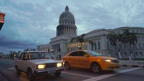 LA HABANA, CUBA - 13 DE MAYO DE 2018 - coches americanos del vintage en los cruces cerca del EL Capitolio en puesta del sol en 4k metrajes