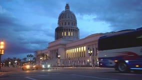 LA HABANA, CUBA - 13 DE MAYO DE 2018 - EL Capitolio en puesta del sol con los coches y la gente americanos del vintage en las cal almacen de metraje de vídeo