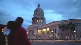 LA HABANA, CUBA - 13 DE MAYO DE 2018 - EL Capitolio en puesta del sol con los coches y la gente americanos del vintage en las cal metrajes