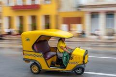 LA HABANA, CUBA - 21 DE OCTUBRE DE 2017: Vehículo amarillo del taxi de Tuk Tuk en La Habana, Cuba La mujer es conductor Foto de archivo libre de regalías