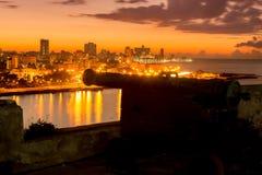 La Habana en la noche con un cañón español viejo Foto de archivo