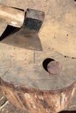 La hache est martelée dans une plate-forme en bois photographie stock libre de droits