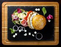 La hamburguesa abierta miente en la teja de la pizarra Foto de archivo libre de regalías