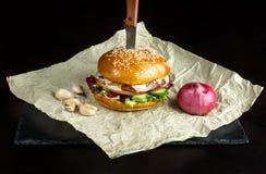 La hamburguesa con ajo está en el papel de Kraft Parte inferior de la pizarra negra Imagen de archivo