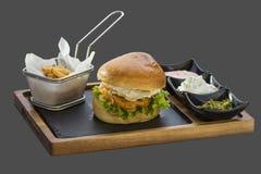 La hamburguesa con la carne frita, adorna las patatas fritas y tres clases o Foto de archivo libre de regalías