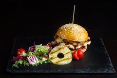La hamburguesa con la piña miente en una pizarra negra surface-2 Fotos de archivo