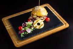 La hamburguesa con la piña miente en una pizarra negra surface-3 Fotografía de archivo libre de regalías