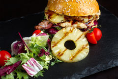 La hamburguesa con la piña miente en una superficie negra de la pizarra Imágenes de archivo libres de regalías