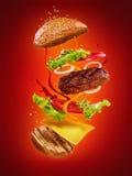 La hamburguesa con los ingredientes del vuelo en fondo rojo Fotos de archivo libres de regalías
