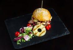La hamburguesa con la piña miente en una pizarra negra surface-3 Foto de archivo
