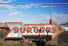 La hamburguesa de neón firma adentro scrapyard de la muestra imagen de archivo