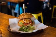 La hamburguesa del bollo del sésamo llenó de la langosta y del camarón Imagen de archivo libre de regalías