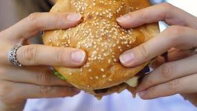 La hamburguesa en manos femeninas se cierra encima de escaparse almacen de video