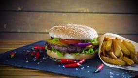 La hamburguesa hecha en casa sabrosa con potatos sirvió en la placa de piedra almacen de video