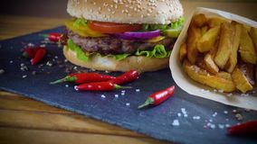 La hamburguesa hecha en casa sabrosa con potatos sirvió en la placa de piedra metrajes
