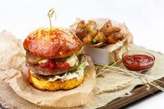 La hamburguesa jugosa de la carne con adorna y sauce en el tablero de madera en pizca Fotos de archivo libres de regalías
