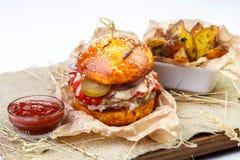 La hamburguesa jugosa de la carne con adorna y sauce en el tablero de madera en pizca Imágenes de archivo libres de regalías