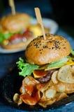 La hamburguesa rústica con las fritadas sirvió en una tabla de madera imagen de archivo