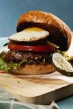 La hamburguesa remató con el huevo soleado en un primer del tablero de madera Fotografía de archivo libre de regalías