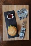La hamburguesa y la baya sauce en el barco de salsa blanco en una base, un vidrio y cubiertos de la pizarra servidos en un tabler Fotografía de archivo libre de regalías