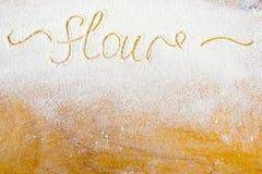 La harina de la palabra escrita en harina en una madera Imágenes de archivo libres de regalías