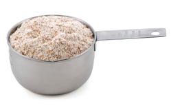 La harina de trigo entero/la harina de trigo/la harina marrón presentaron en una medida de la taza fotografía de archivo libre de regalías