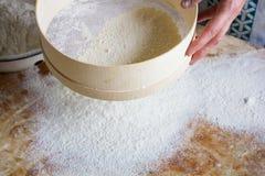 La harina se tamiza a través de un tamiz de madera Fotografía de archivo libre de regalías