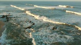 La haute altitude aérienne au-dessus du blanc approximatif ondule se briser sur la plage au lever de soleil banque de vidéos