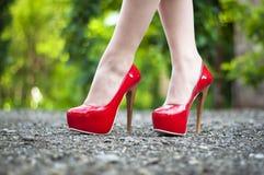 La haute femelle a gîté les chaussures rouges sur le chemin devant le fond vert Photos stock