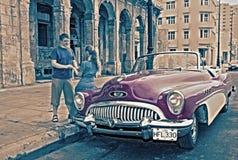 LA HAVANE, CUBA 27 JANVIER 2013 : jeune femme et de type cabriolet ouvert près le rétro sur la rue à vieille La Havane, Cuba rétr Images libres de droits