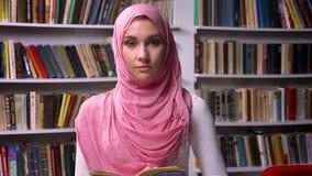 La hembra árabe feliz en hijab rosado se está colocando en la biblioteca y la sonrisa alegres, humor de Oriente Medio, lugar rese almacen de metraje de vídeo
