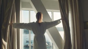 La hembra abre las cortinas en una ventana almacen de video