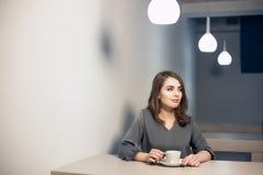 La hembra adulta joven tiene descanso para tomar café en café; Fotografía de archivo libre de regalías