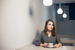 La hembra adulta joven tiene descanso para tomar café en café; Imagen de archivo libre de regalías