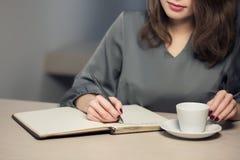 La hembra adulta joven tiene descanso para tomar café en notas del café y de la escritura en diario o libreta; Fotos de archivo