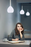 La hembra adulta joven tiene descanso para tomar café en notas del café y de la escritura en diario o libreta; Fotos de archivo libres de regalías