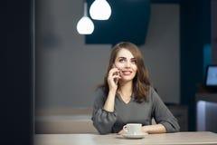 La hembra adulta joven tiene el descanso para tomar café en café y hablar en el teléfono Fotos de archivo libres de regalías