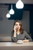 La hembra adulta joven tiene el descanso para tomar café en café y hablar en el teléfono Fotografía de archivo