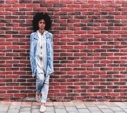 La hembra afroamericana se está inclinando contra una pared de ladrillo al aire libre Foto de archivo