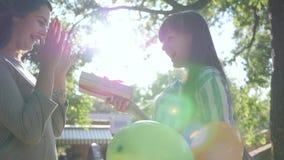 La hembra alegre con los globos coloridos felicita el feliz cumpleaños en parque, sorpresa del amigo de los presentes almacen de metraje de vídeo