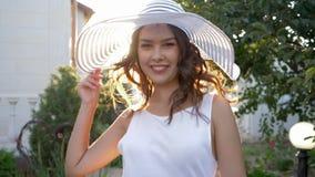 La hembra alegre en el sombrero elegante camina y gira en primer de los rayos solares metrajes