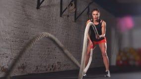 La hembra atlética en un gimnasio ejercita activamente con las cuerdas de la batalla durante su entrenamiento cruzado de la aptit almacen de video