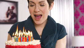 La hembra atractiva alista para soplar hacia fuera velas de la torta de cumpleaños Foto de archivo libre de regalías